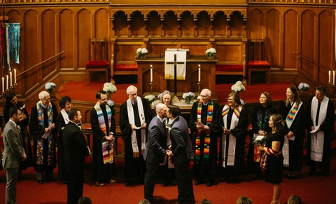 Thomas Phillips and Caleb Parker kiss during their Feb. 29 wedding in Durham. Twelve United Methodist ministers risked discipline from the international church for participating in the same-sex wedding. (Photo by Tammy Jean Lamoureux of L'Amour Foto).