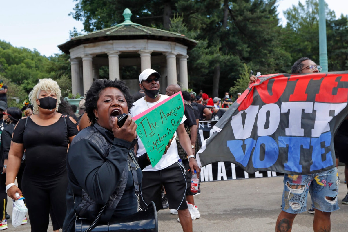"""Holding a sign that reads, """"The American system is rigged,"""" a woman amplifies her voice as she implores protesters to rise to the occasion and become activists during a Caribbean-led Black Lives Matter rally at Brooklyn's Grand Army Plaza, Sunday, June 14, 2020, in New York. Image via AP Photo/Kathy Willens)"""