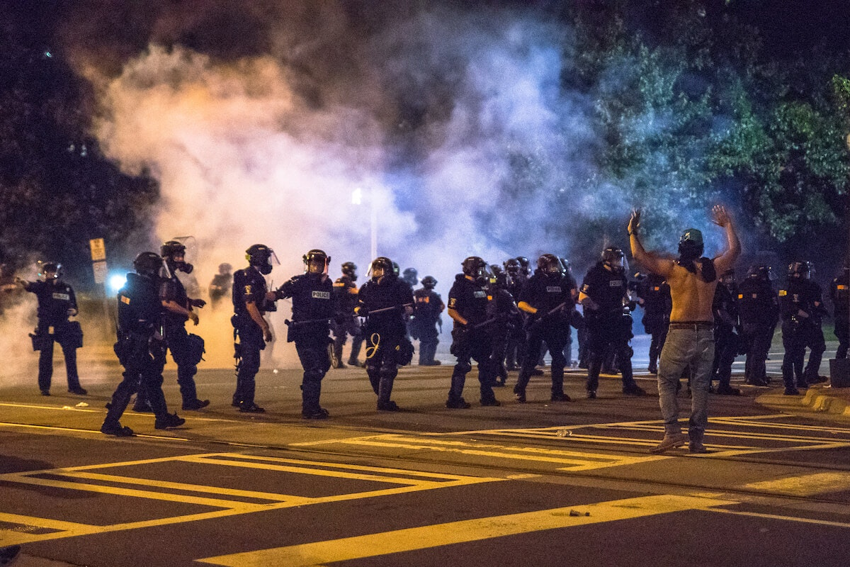 Protesters confront Charlotte officers during a demonstration in May. (Photo for Cardinal & Pine by Grant Baldwin).
