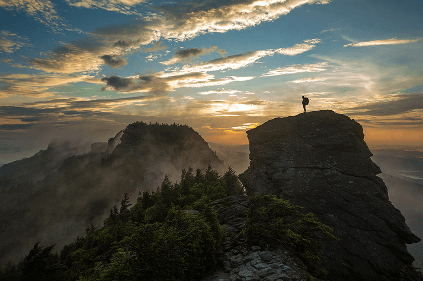 A hiker on top of Grandfather Mountain. Image via Visit NC.
