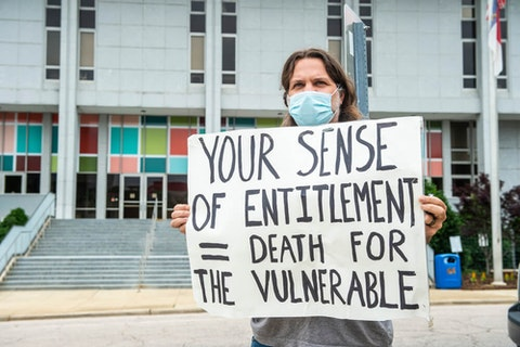A demonstrator in Raleigh advocates for social distancing and masks. After weeks of pressure, Gov. Cooper ordered a mask rule Wednesday. (Image via Shutterstock)
