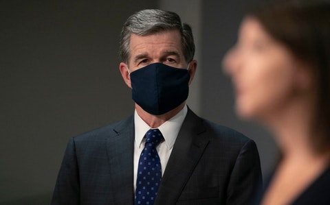 Governor Roy Cooper listens to Dr. Mandy Cohen, Secretary of the North Carolina Department of Health and Human Services, during their press briefing on the COVID-19 virus at the Emergency Operations Center on Tuesday, July 28, 2020 in Raleigh. (Image via NC DPS)