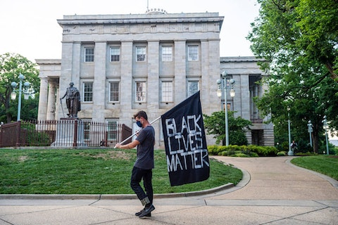 A demonstrator marches in front of the State Capitol in Raleigh in June. The Capitol has been the scene of multiple protests of racial inequality in 2020. (Image via Shutterstock)
