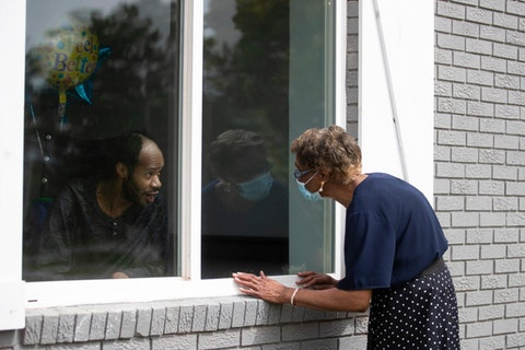 Window visits have become a common scene as relatives try to visit nursing home residents during the Pandemic. (AP Photo/John Bazemore)