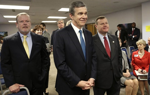 In this May 2018, file photo, from left, Senate President Pro Tempore Phil Berger, North Carolina Gov. Roy Cooper and House Speaker Tim Moore pause prior to a news conference in Raleigh, N.C. The legislature and Cooper have been bitterly at odds over Medicaid expansion, although this year's election has the potential to break the logjam. (AP Photo/Gerry Broome, File)