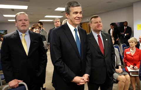 In this May 2018, file photo, from left, Senate President Pro Tempore Phil Berger, North Carolina Gov. Roy Cooper and House Speaker Tim Moore pause prior to a news conference in Raleigh, N.C. The legislature and Cooper arrived at a deal Wednesday on school reopening during the pandemic. (AP Photo/Gerry Broome, File)