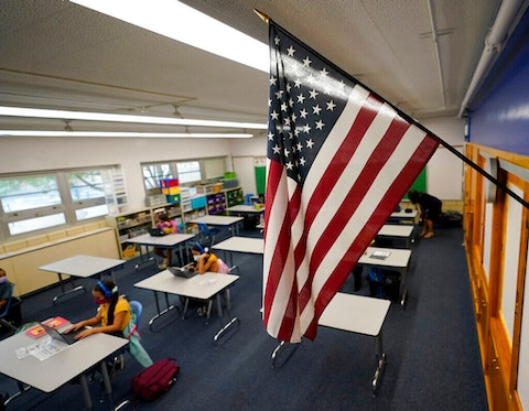 An American flag is in a classroom as students work on laptops in Newlon Elementary School early Tuesday, Aug. 25, 2020, which is one of 55 Discovery Link sites set up by Denver Public Schools where students are participating in remote learning in this time of the new coronavirus from a school in Denver. (AP Photo/David Zalubowski)