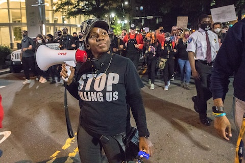 Kass Ottley, leader of Seeking Justice CLT, leads chants during a march through uptown Charlotte in response to the Breonna Taylor case in September. (Image for Cardinal & Pine by Grant Baldwin)