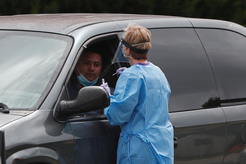 A drive-up patient is assisted with testing at a community coronavirus test site operated by Cone Health and the county Health Department in Burlington in July. (AP Photo/Gerry Broome)