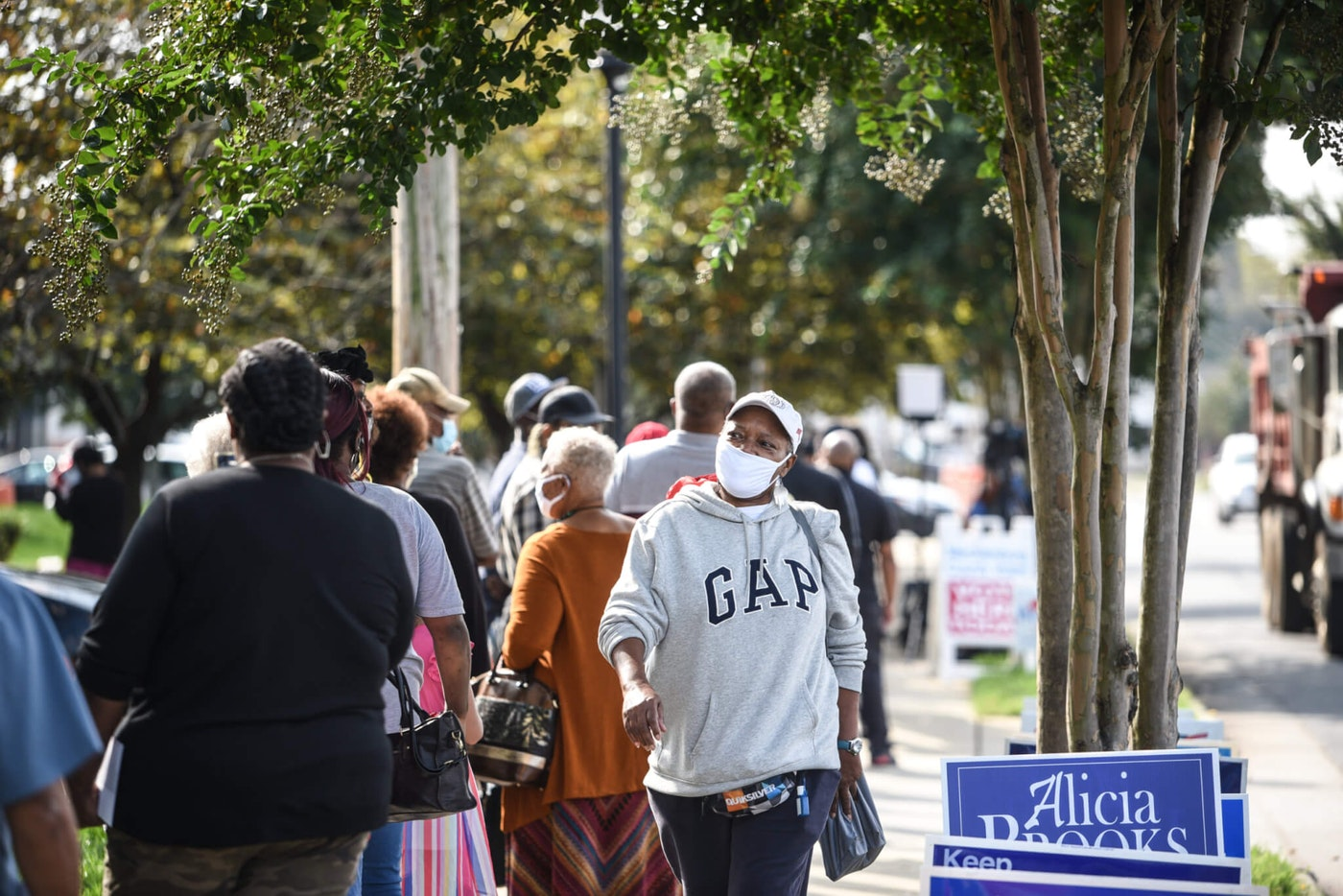 Voters stand in line waiting to cast ballots in  the 2020 election at a Charlotte early voting site. (Photo for Cardinal & Pine by Alvin Jacobs Jr.)