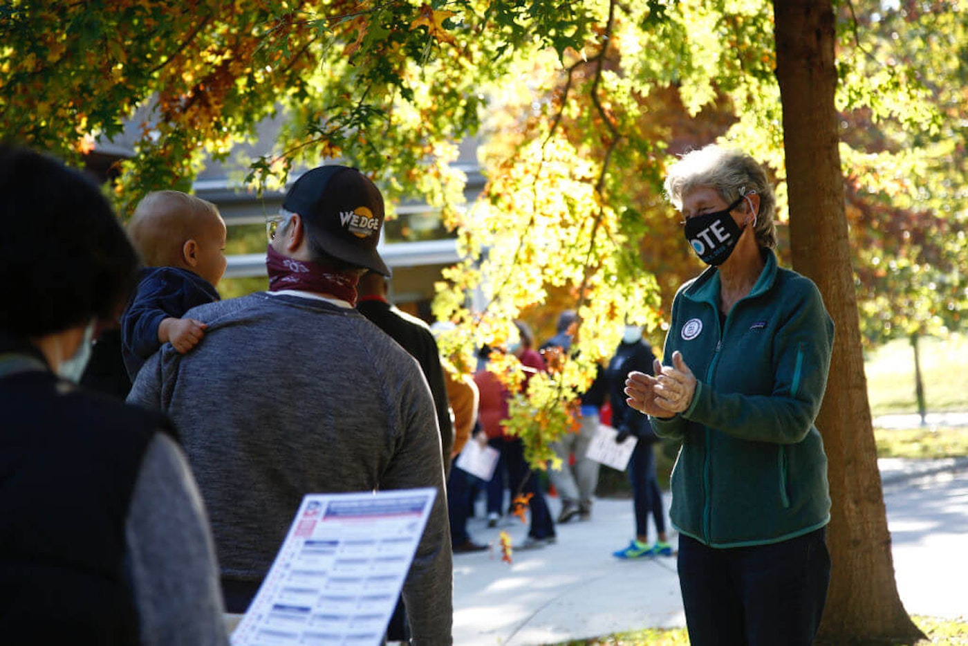 ASHEVILLE, NC - OCTOBER 15:  Susan Presson, a volunteer with the Buncombe County Democratic Party, speaks with voters waiting in line to vote at a polling place at the Dr. Wesley Grant Senior Center on October 15, 2020 in Asheville. Record numbers came out for in-person, early voting. State officials expect half of NC's registered voters will have cast ballots by day's end Wednesday. (Photo by Brian Blanco/Getty Images)
