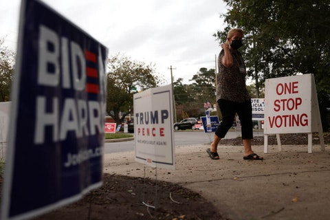 FAYETTEVILLE, NORTH CAROLINA - OCTOBER 29: A woman walks pass campaign signs displayed outside an early voting location at Kiwanis Recreation Center on October 29, 2020 in Fayetteville, North Carolina. (Photo by Alex Wong/Getty Images)