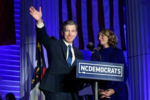 North Carolina Gov. Roy Cooper, joined by his wife Kristin, reacts after being declared winner over Republican Dan Forest in the governor's race in Raleigh, N.C., Tuesday, Nov. 3, 2020. State election officials certified the governor's race and most in the state Tuesday, Nov. 24. (AP Photo/Gerry Broome)