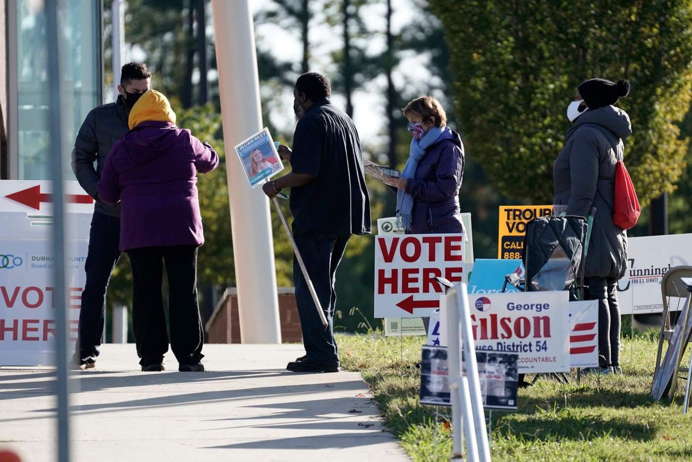 Voters are assisted at a polling location at the South Regional Library in Durham, N.C., Tuesday, Nov. 3, 2020. (AP Photo/Gerry Broome)