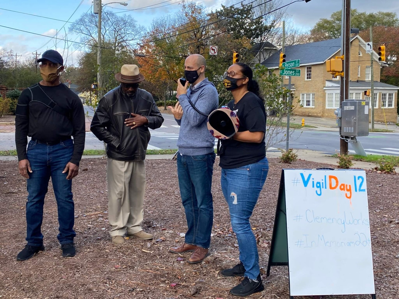 Jamie Lau, center, speaks in a vigil calling on Gov. Roy Cooper to act on pardon and clemency requests with two of his clients released from prison after serving long sentences next to him, Calrutha Johnson  and Ronnie Long. Kristie Puckett-Willliams of the ACLU of NC is on the right. (Image courtesy of Melissa Boughton)