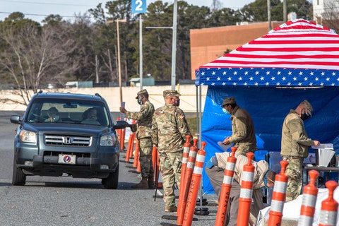 National Guard soldiers assist by directing those arriving for vaccination appointments at Bojangles Arena in Charlotte, NC, the primary site of vaccine distribution for Mecklenburg County. (Image for Cardinal & Pine by Grant Baldwin)