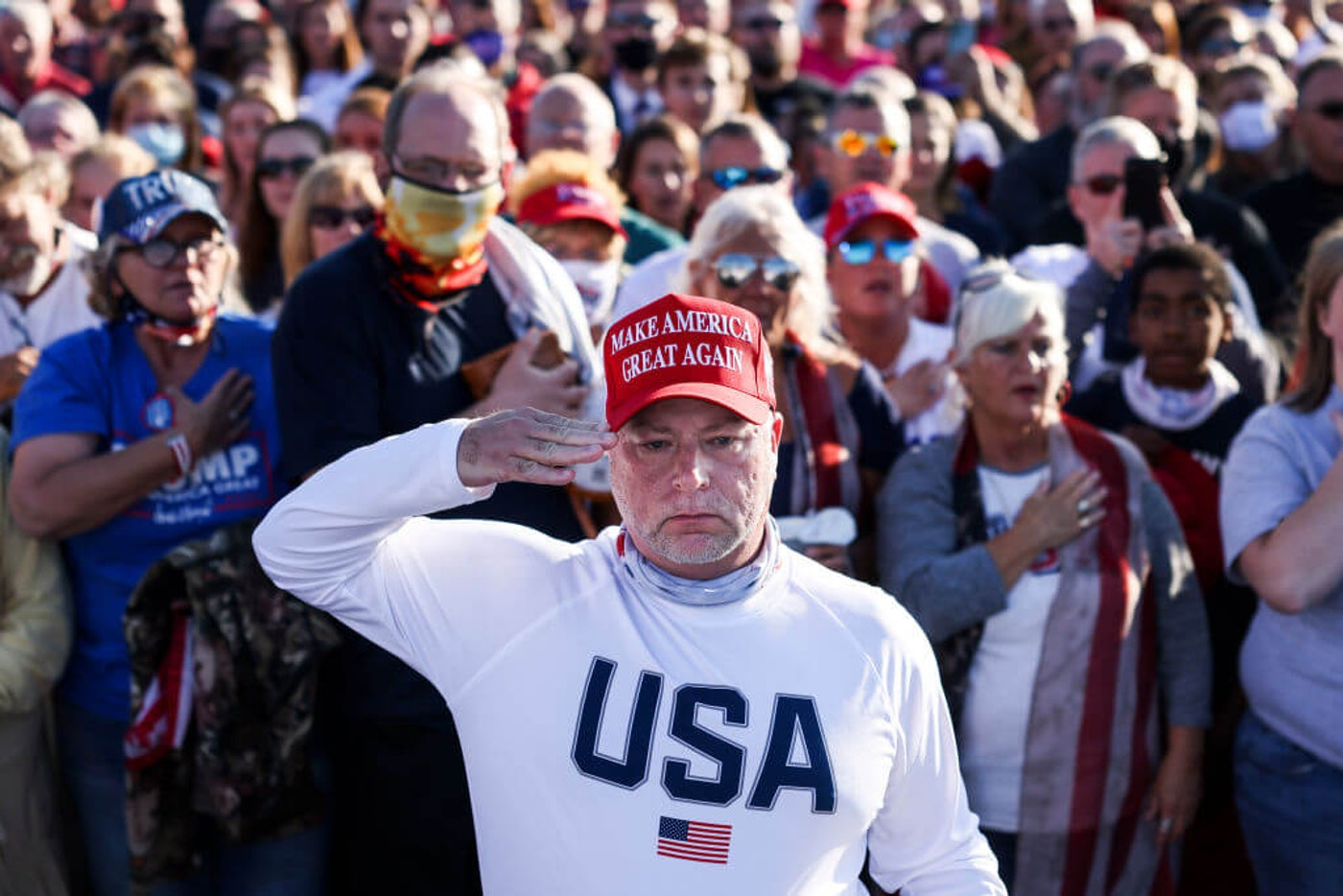 A man salutes during the national anthem as a crowd waits for President Donald Trump to speak at a rally at the Hickory Regional Airport on November 1, 2020 in Hickory, North Carolina. (Photo by Michael Ciaglo/Getty Images)
