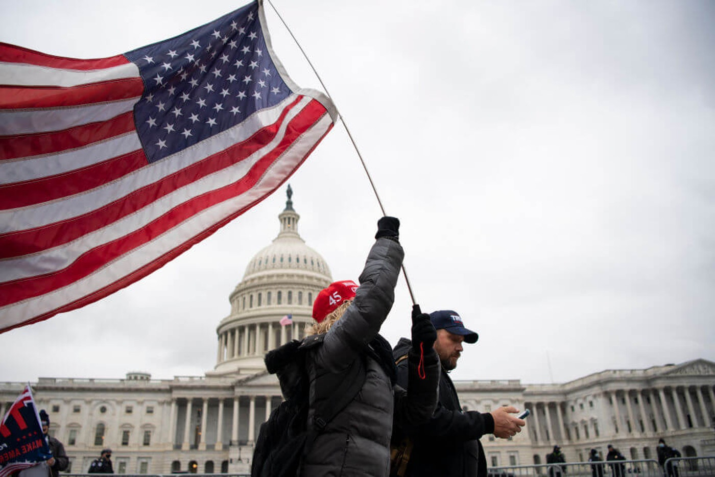 A demonstrator holds an American flag during a Trump rally along the East Front of the Capitol in Washington on Tuesday, Jan. 5, 2021. (Photo by Caroline Brehman/CQ-Roll Call, Inc via Getty Images)