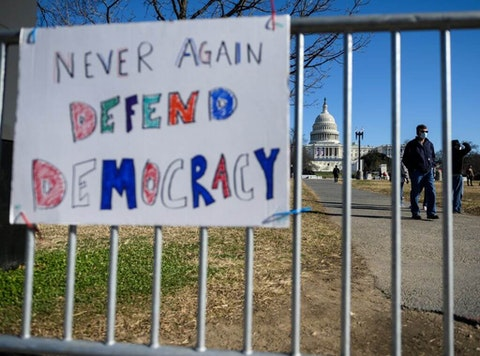 People pass signs of support near the US Capital in Washington, DC on January 10, 2021. - Donald Trump faced fresh calls Sunday from some members of his own party to resign over the violent incursion into the US Capitol, as the threat builds for a historic second impeachment effort in his final 10 days in the White House. (Photo by Andrew CABALLERO-REYNOLDS / AFP)