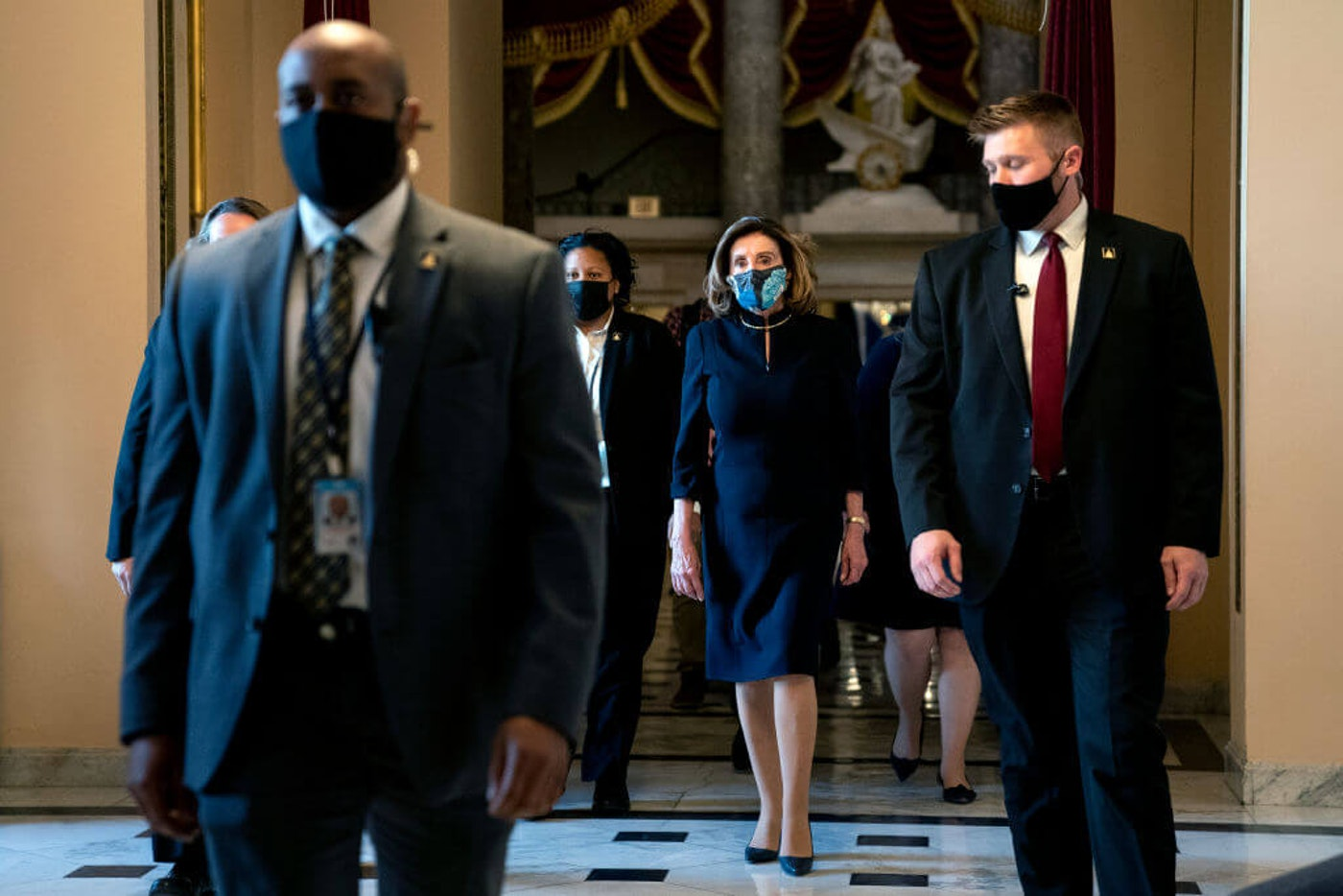 WASHINGTON, DC - JANUARY 13: Speaker of the House Nancy Pelosi (D-CA) (C) wears a protective mask while walking to the House Floor during a vote on the impeachment of President Donald Trump at the U.S. Capitol on January 13, 2021 in Washington, DC. The House of Representatives moved forward with impeachment following Vice President Mike Pences refusal to use the 25th amendment to remove Trump from office after protestors breached the U.S. Capitol last week. (Photo by Stefani Reynolds/Getty Images)