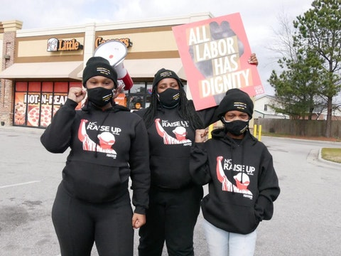 From L to R: Kyona Kelley, Porche Vann, Yeshera Douglas protest for higher wages outside a Little Caesar's in Fayetteville.