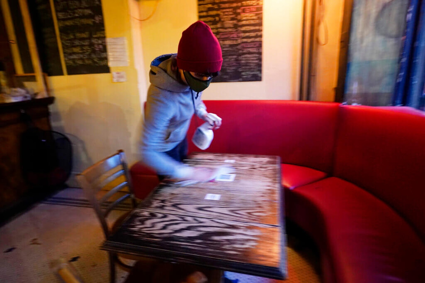 Bartender Alex Wright sanitizes a table before opening Barbès, a popular neighborhood music venue and bar converted to a bottle shop and mostly-outdoor bar during the the coronavirus pandemic in New York in December. (Image via AP Photo/Kathy Willens)
