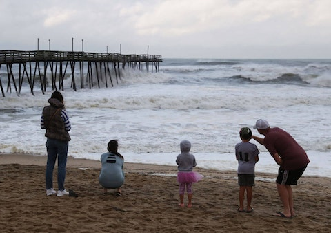 People look out at the Avalon Pier that was damaged by Hurricane Dorian in Kill Devil Hills in 2019. Local health officials say hurricane response prepared them for their successful COVID vaccine drive. (Photo by Mark Wilson/Getty Images)