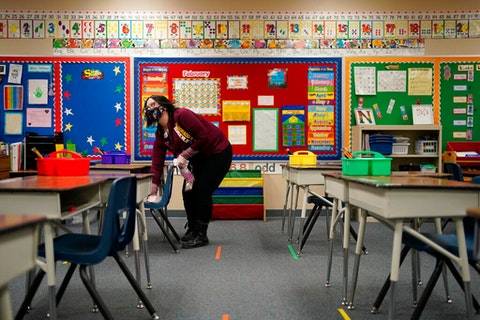 Tia Baker cleans a desk in a classroom during a media tour at Dorothy Eisenberg Elementary School, Thursday, Feb. 25, 2021, in Las Vegas. (Image via AP Photo/John Locher)