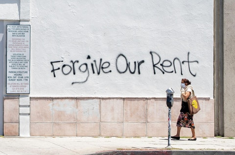 A woman wears a mask as she passes a grafitt message in Los Angeles in May 2020. (Image  via Getty Images)
