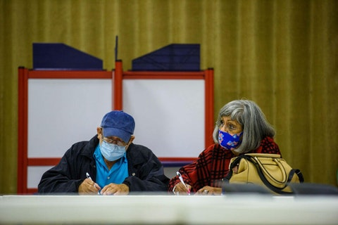 A couple fills out ballots together at the O.P. Owens Building on November 3, 2020  in Lumberton, North Carolina.  After a record-breaking turnout during the 2020 election, Democrats and Republicans are at odds over Democrats plans to expand voting access through the 'For the People Act.' (Photo by Melissa Sue Gerrits/Getty Images)