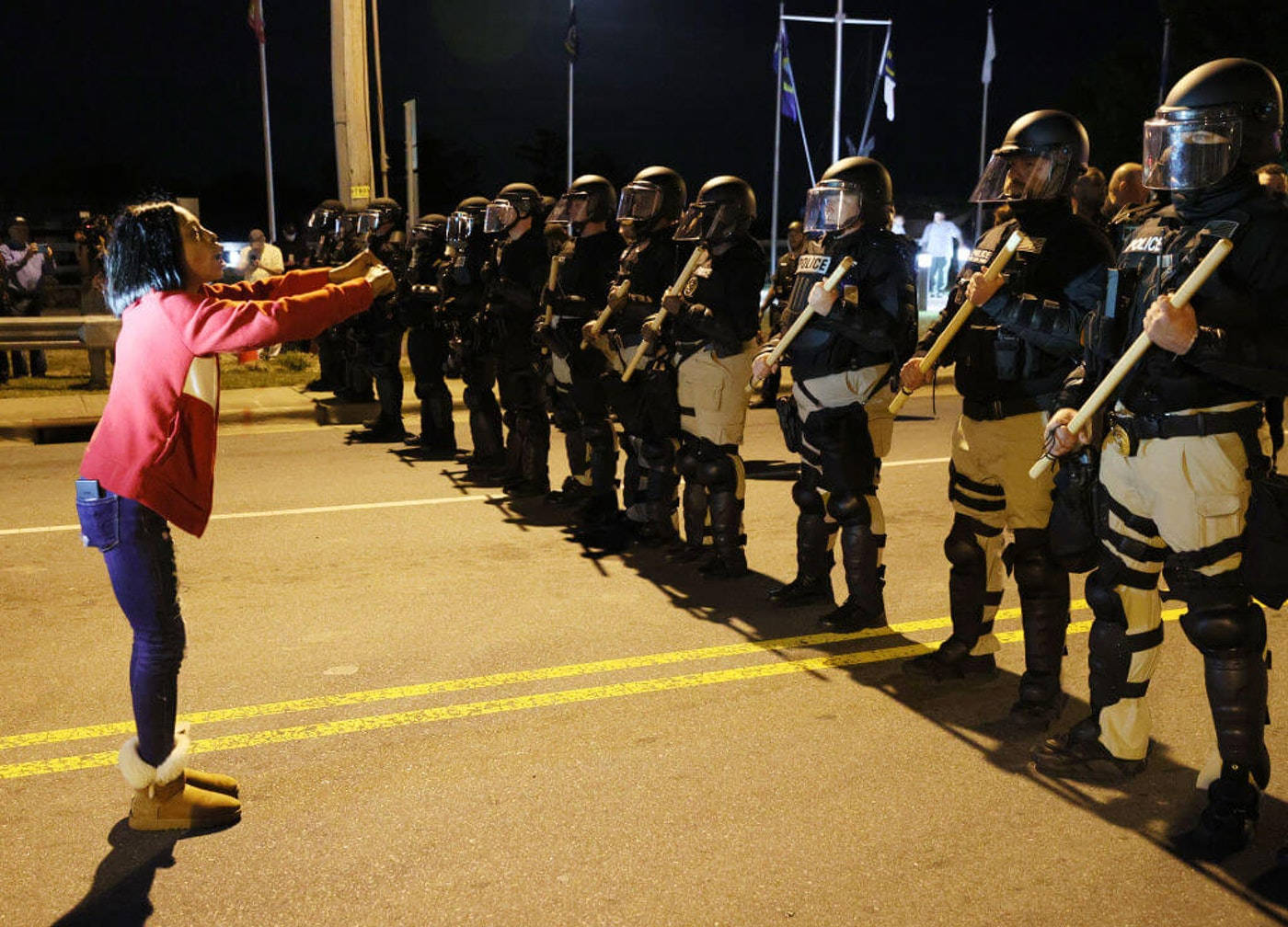 ELIZABETH CITY, NORTH CAROLINA - APRIL 27: Patrice Revelle stands in front of police in riot gear as they force people off a street as they protest the killing of Andrew Brown Jr. on April 27, 2021 in Elizabeth City, North Carolina. The police were enforcing an 8 pm curfew announced after the shooting death of Brown by Pasquotank County Sheriff deputies on April 21.  (Photo by Joe Raedle/Getty Images)