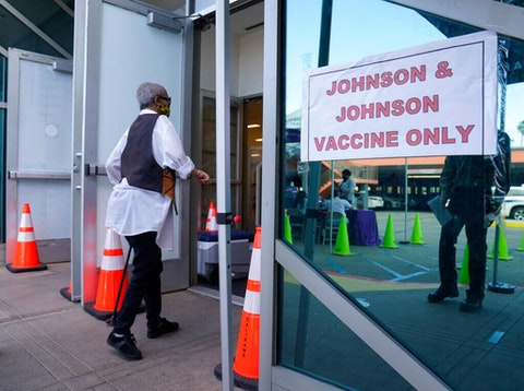 "People walk in to get their COVID-19 vaccine at the Baldwin Hills Crenshaw Plaza past a sign that says ""Johnson & Johnson vaccine only"" in Los Angeles (Image via AP Photo/Damian Dovarganes, File)"