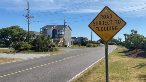 A sign warns motorists and others of flooding on New River Inlet Road, in North Topsail Beach. A 2019 study by the Center for Climate Integrity, estimates that it will cost $724 million to adequately provide short term protection against flooding in N. Topsail. (Photo by Michael McElroy)