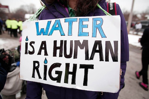 In this 2016 file photo, people gather in front of a Flint, Mich. church before participating in a national march to highlight the push for clean water. (Image via Bill Pugliano/Getty Images)