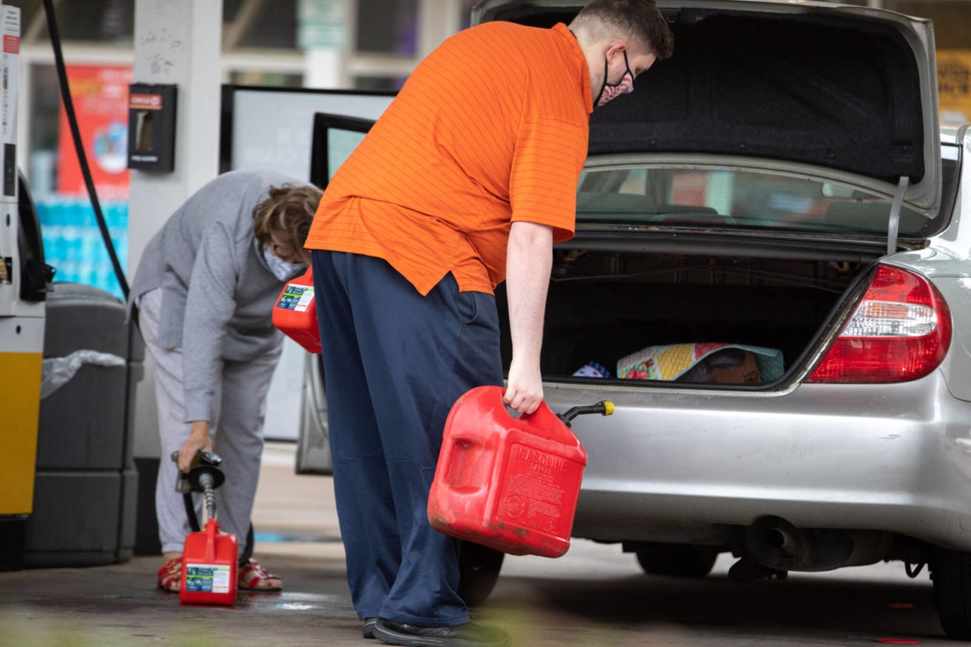 A person in an orange shirt accompanied by another in gray load numerous gas containers into a sedan at a Charlotte, NC gas station.