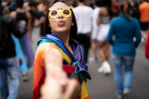 A young feminine-presenting person in a rainbow cape and yellow goggles holds a hand out in invitation to the viewer. Crowds in the background appear to be celebrating.