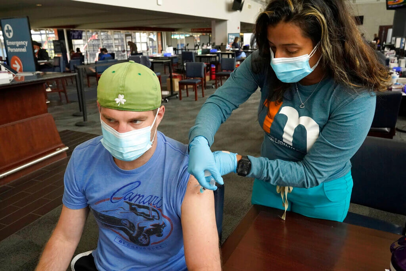 Kevin Fisher, of Quincy, Mass., left, receives his second shot of Moderna COVID-19 vaccine from RN Katherine Francisco, of Avon, Mass., right, at a mass vaccination clinic, Wednesday, May 19, 2021, at Gillette Stadium, in Foxborough, Mass. A month after every adult in the U.S. became eligible for the vaccine, a distinct geographic pattern has emerged: The highest vaccination rates are concentrated in the Northeast, while the lowest ones are mostly in the South. (AP Photo/Steven Senne)