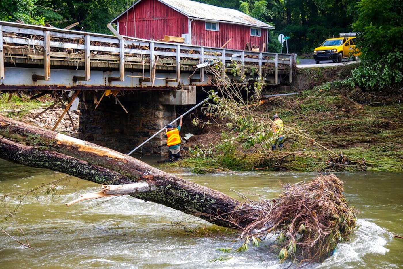 NCDOT workers assess damage to a bridge spanning the Pigeon River, Thursday in Bethel, N.C., (Travis Long/The News & Observer via AP)