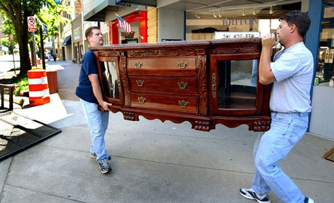 In this 2004 file photo, off-duty Greensboro, NC firefighters Kevin Ozment, left, and Mark Cockman carry their purchased cabinet to a trailer from the Crown Mark furniture store in downtown High Point, NC. High Point is touted as the furniture capitol of the world.  (Photo by Gina Ferazzi/Los Angeles Times via Getty Images)