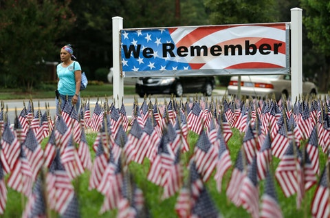 A woman walks past thousands of flags placed to honor of the victims of the 9/11 terrorist attacks in Charlotte in 2015. North Carolina will commemorate the 20th anniversary of Sept. 11 this weekend with dozens of events across the state. (AP Photo/Chuck Burton)