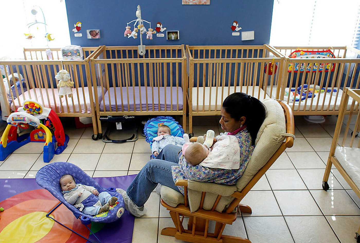 Daycare employee Remontia Greene tends to three infants in a preschool in Clayton, NC, in 2009.  Local leaders in North Carolina are touting the potential for two major infrastructure bills in DC to impact childcare as well as community colleges and broadband internet. (Photo by Ted Richardson/Raleigh News & Observer/Tribune News Service via Getty Images)