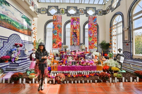 """The grueling COVID-19 pandemic changed the way Charlotte artist Rosalia Torres Weiner created her annual Dia De Los Muertos altar, or """"ofrenda,"""" which will be debuted this weekend in Charlotte. Here, Torres Weiner shows off her work in 2017 at the Mexican Cultural Institute in Washington D.C. (Photo by Sergio Ochoa courtesy of Torres Weiner)"""
