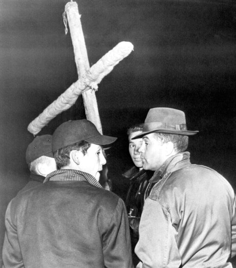 This Associated Press file photo show a group of Lumbee Native Americans in Maxton in front of a crude cross they captured during a gun battle with members of the Ku Klux Klan in 1958. (Photo via AP Photo)