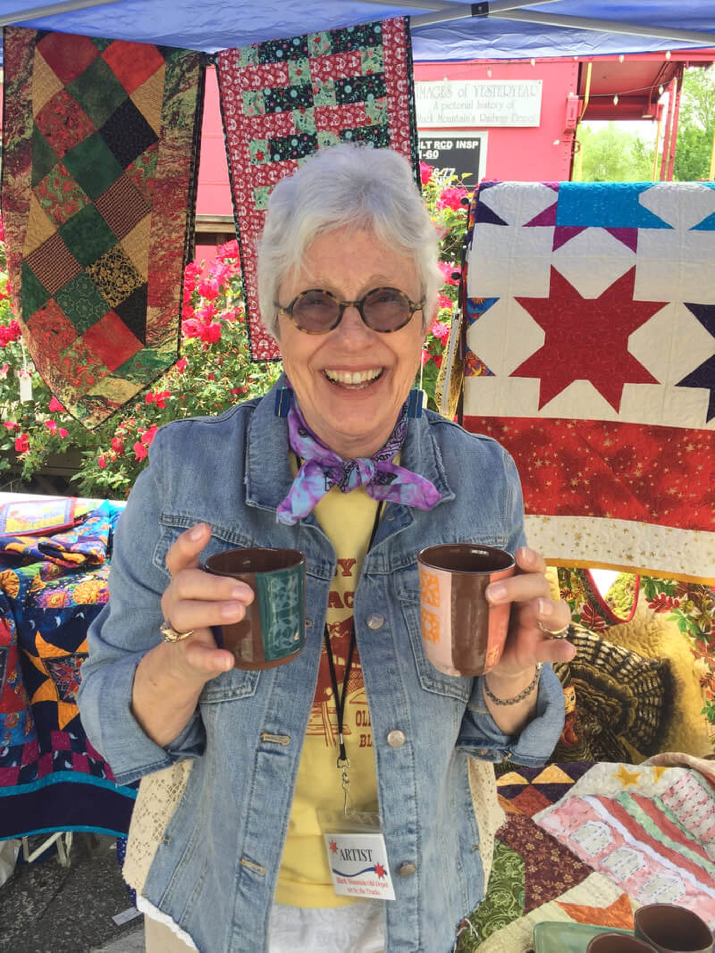 Grey[haired person in sunglasses and denim jacket stands before a quilt display holding up two mugs in welcome.