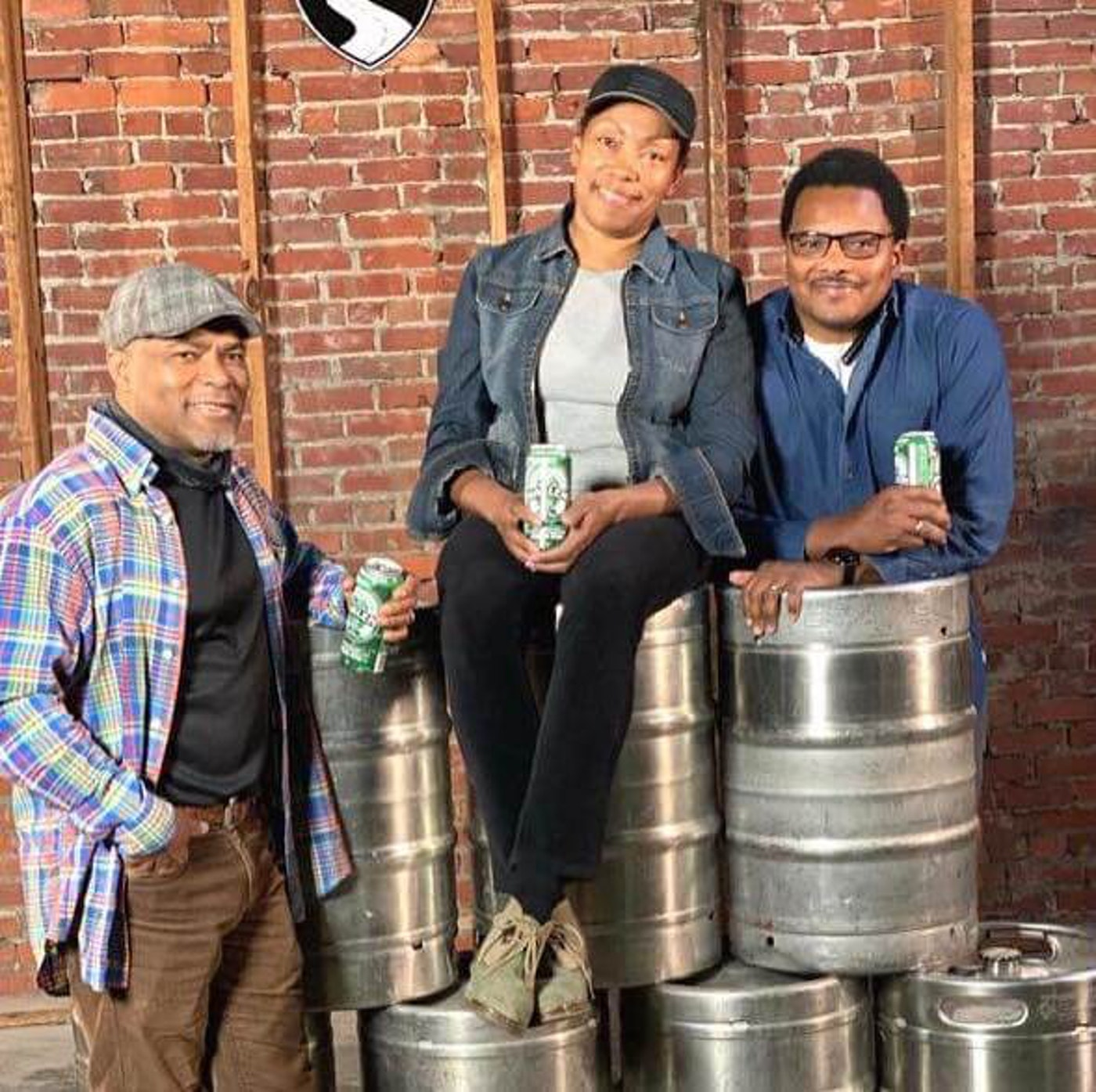 Carl (left) and Pernell Beatty (right) flank their sister Celeste, the owner of Harlem Brew South, in her taproom. The warehouse is the site of Operation Dixie, a historical and successful labor campaign in 1946. More than 10,000 tobacco workers, mostly women, gathered from around the state and voted to unionize for better working conditions. Harlem Brew's lager is named '1946' in tribute.