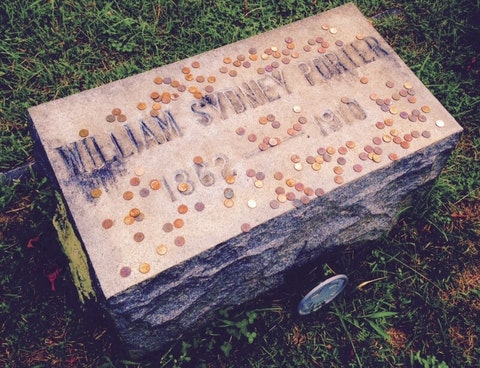 """To commemorate the first few lines of his short story """"The Gift of the Magi,"""" fans still leave $1.87 in change on the North Carolina grave of legendary writer O. Henry. (Image via Historic Riverside Cemetery in Asheville)"""