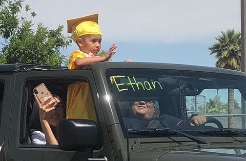 child in graduation cap and gown waves from a car's sunroof