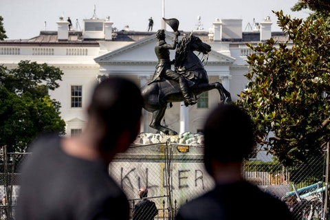"Anthony Davis of Upper Marlboro, Md., left, speaks to his son Jonathan, 13, right, as they look at a statue President Andrew Jackson in Lafayette Park, Tuesday, June 23, 2020, in Washington, with the word ""Killer"" spray painted on its base. Protesters tried to topple the statue Monday night. President Tump had tweeted late Monday that those who tried to topple the statue of President Andrew Jackson in Lafayette Park across the street from the White House faced 10 years in prison under the Veteran's Memorial Preservation Act.  (AP Photo/Andrew Harnik)"