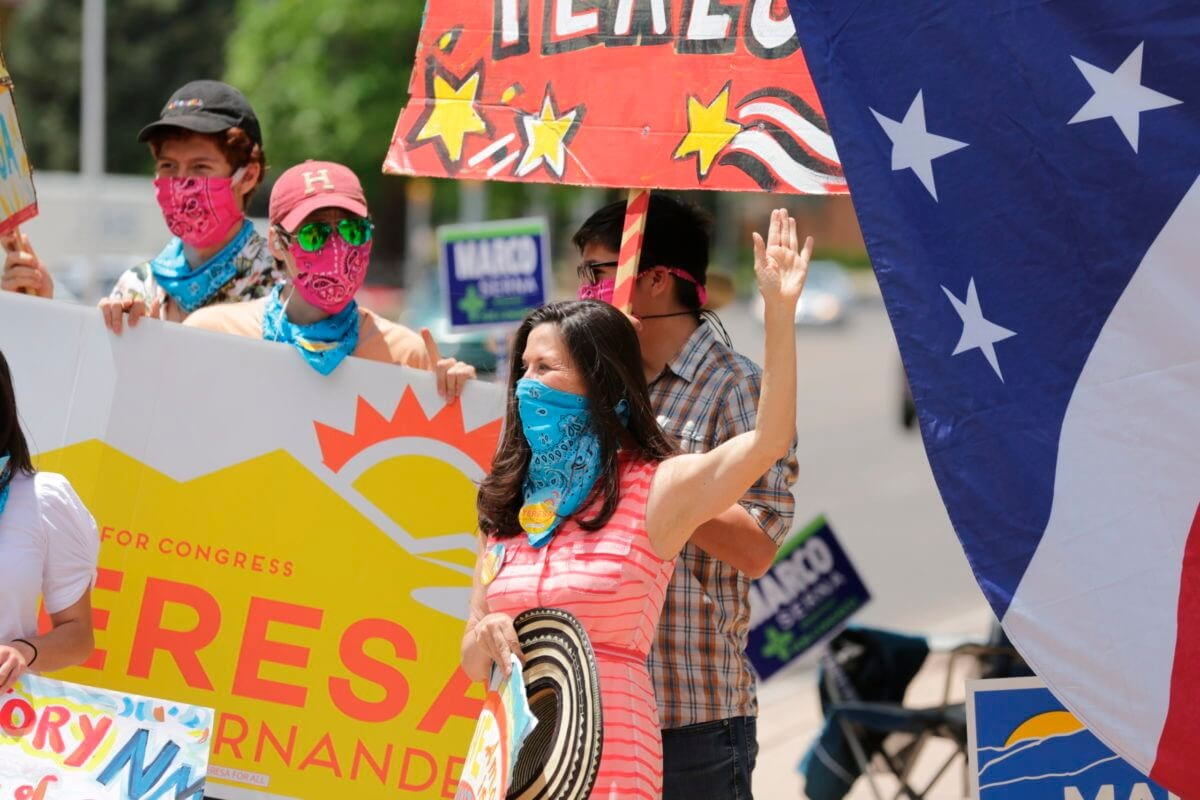 Democratic congressional candidate Teresa Leger Fernandez, in the blue mask, cheers on supporters at a polling station Tuesday, June 2, 2020, in Santa Fe, N.M. (AP Photo/Cedar Attanasio)