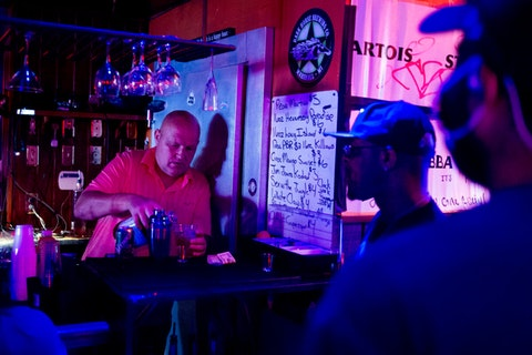 In this June 8, 2020, file photo, Rodney Ott, owner of The Loft, makes mixed drinks from behind the bar for patrons as he reopens fully for the first time amid the coronavirus outbreak in downtown Flint, Mich.